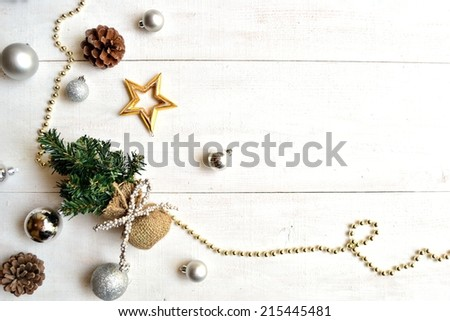 Christmas tree with silver ornaments on white wooden background