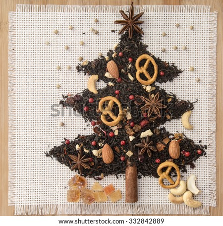 Christmas tree with tea, coffee beans, dried fruits, nuts and spices on a linen napkin, top view, Homemade christmas cookies  - stock photo