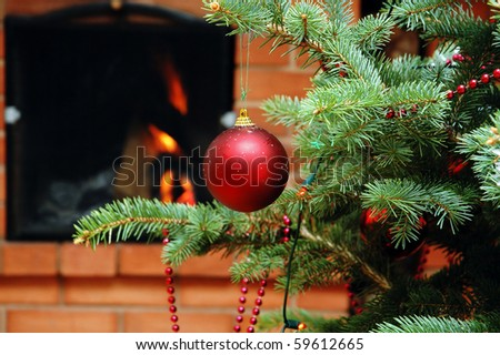 Christmas tree with toy with fireplace as background - stock photo