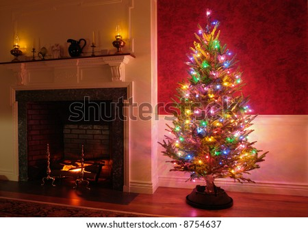 Christmas tree with vintage multicolor lights in an old fashioned traditional house interior with brick fireplace and warm burning fire log in hearth - stock photo