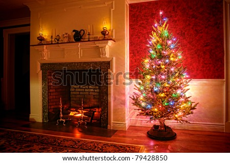 Christmas tree with vintage multicolor lights in an old fashioned traditional interior with brick fireplace and warm burning fire log in hearth - stock photo