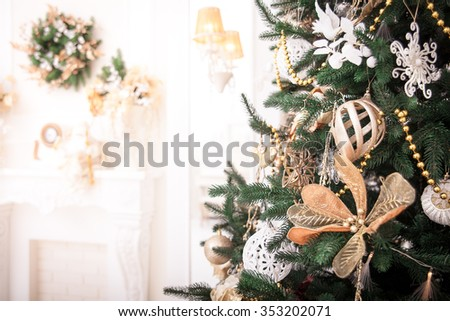 Christmas tree with white and gold toys and decorations.
