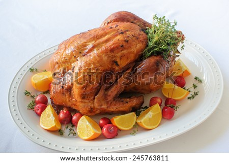 Christmas turkey on the big white plate with thyme, baby apples and oranges