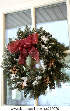 Christmas twig wreath with snow on house door - stock photo