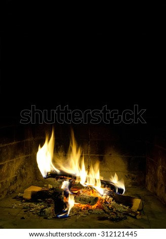 Christmas vacation postcard template. Chimney place against dark background. Flames of fire in a fireplace. Realistic fire. Copy space, black background. - stock photo