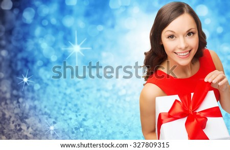 christmas, valentines day, birthday, people and holidays concept - smiling woman in red dress with gift box over blue glitter or lights background - stock photo