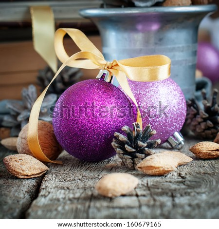 Christmas Violet  Balls with ribbon, pine cones, almonds at the Wooden Table - stock photo