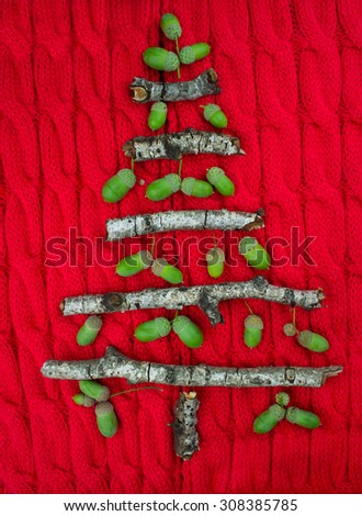 Christmas warm knitted background with new year tree decorations made of sticks and acorns. Vintage christmas card with handmade christmas tree. X-mass concept. - stock photo