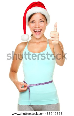 Christmas weight loss concept. Fitness woman wearing santa hat measuring waist with measure tape showing thumbs up smiling happy. young multi-cultural female model isolated on white background.