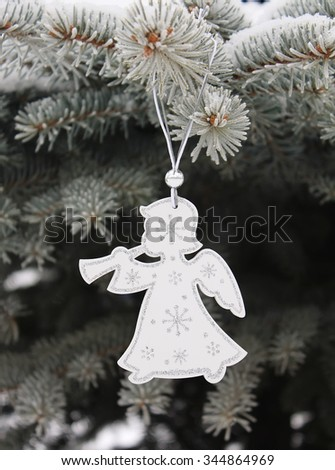 Christmas white angel with silvery snowflakes on christmas tree - stock photo