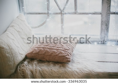 Christmas window  with knitted cushions - stock photo