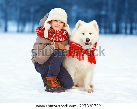 Christmas, winter and people concept - happy teenager boy walking with white Samoyed dog outdoors in winter day - stock photo