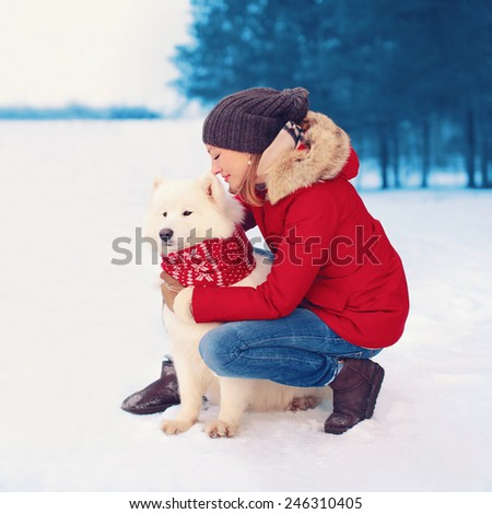 Christmas, winter and people concept - happy woman owner embracing white Samoyed dog outdoors - stock photo