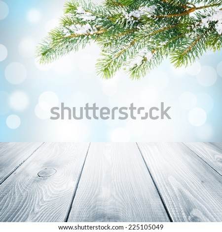 Christmas winter background with snow fir tree, wooden table and blurred bokeh - stock photo