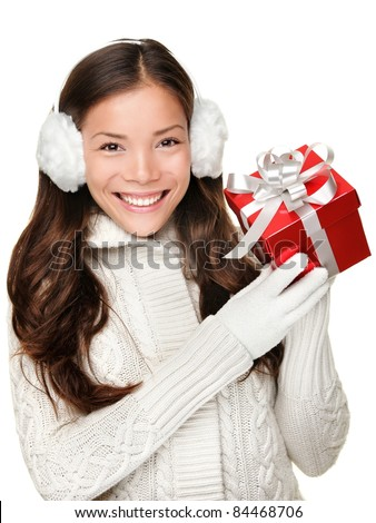 Christmas winter girl holding red present wearing warm sweater and ear muffs. Young beautiful and cute multi-racial woman with lovely smile isolated on white background. - stock photo