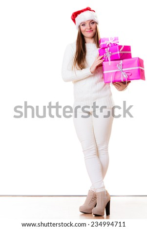 Christmas winter happiness concept. Woman in full length wearing santa helper hat holding stack of pink presents gift boxes isolated on white