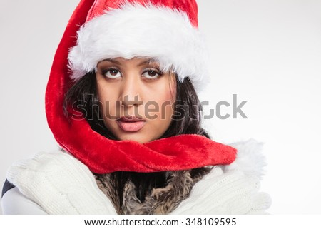 Christmas winter happiness concept. Young woman girl mixed race wearing santa helper hat fur portrait. Gray background