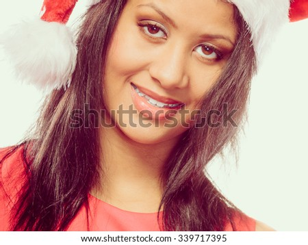 Christmas winter happiness concept. Young woman girl mixed race wearing santa helper hat portrait. Instagram fliter