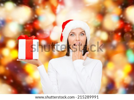 christmas, winter, happiness, holidays and people concept - smiling woman in santa helper hat with gift box over red lights background - stock photo