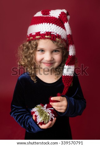 Christmas, Winter Holiday themed setup: beautiful child in santa elf hat on red background - stock photo