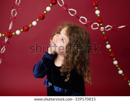 Christmas, Winter Holiday themed setup: beautiful child ornaments and decorations on red background, pointing - stock photo