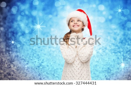 christmas, winter, holidays and childhood concept - dreaming girl in santa helper hat over blue glitter or lights background