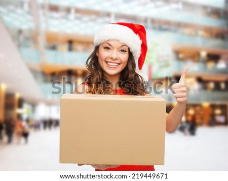 christmas, winter holidays, delivery, gesture and people concept - smiling woman in santa helper hat with parcel box showing thumbs up over shopping center background - stock photo