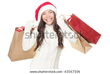 Christmas winter shopping. Woman in santa hat standing holding shopping bags excited isolated on white background. Young mixed race Asian Chinese / white Caucasian model. - stock photo