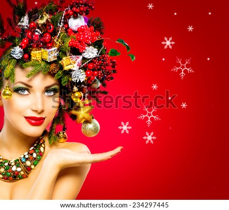 Christmas Winter Woman. Beautiful New Year and Christmas Tree Holiday Hairstyle and Make up. Beauty Fashion Model Girl over holiday red Background. Creative Hair style decorated with Baubles. Hand - stock photo