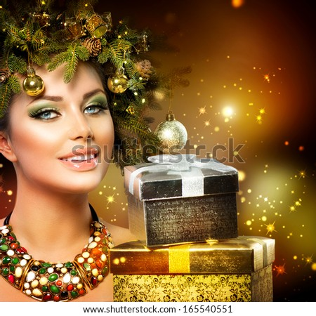 Christmas Winter Woman with Christmas Gifts. Fairy. Beautiful New Year and Christmas Tree Holiday Hairstyle and Make up. Magic. Beauty Fashion Model Girl With Present Box. Holiday Magic stars.  - stock photo