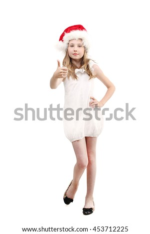 christmas, winter, x-mas, holidays and childhood concept - standing smiling girl in santa helper hat gesturing thumbs up isolated over white background - stock photo