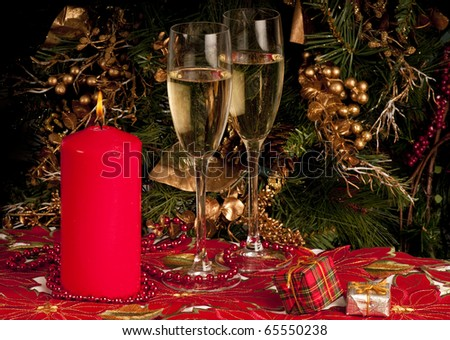 Christmas with Christmas table cloth,  small presents, candles, christmas decorations champagne and wine glass, party - stock photo