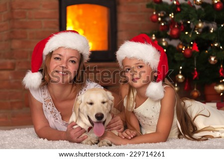 Christmas with our doggy - woman and little girl and the family pet - stock photo