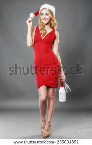 Christmas woman beautiful smiling with glass of champagne santa's hat isolated on gray background - stock photo