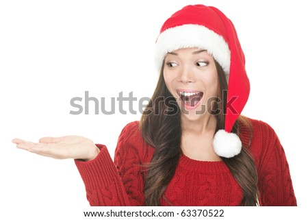 Christmas woman copy space. Excited santa girl presenting your product looking sideways on copyspace with open hand palm. Closeup of mixed Asian Caucasian female model isolated on white background. - stock photo