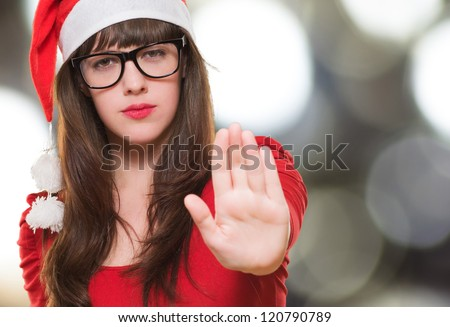 christmas woman doing a stop gesture against an abstract background - stock photo