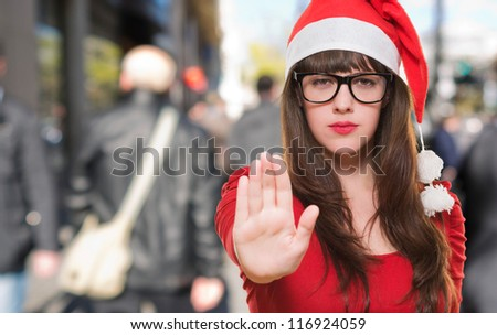 christmas woman doing a stop gesture, outdoor - stock photo