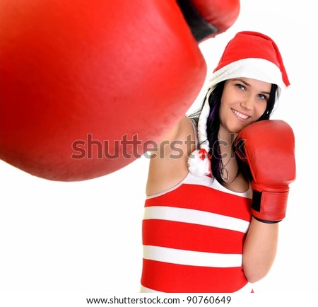 Christmas woman hitting wearing boxing gloves and red santa hat, model isolated on white background.