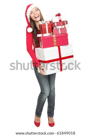 Christmas woman holding gifts wearing Santa hat. Standing in full body isolated on white background. Smiling woman portrait of a beautiful mixed Asian / Caucasian model. - stock photo