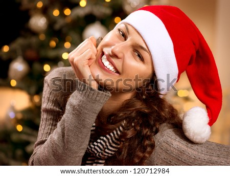 Christmas Woman in Santa Hat.Happy Smiling Girl Celebrating New Year at Home.Christmas Tree