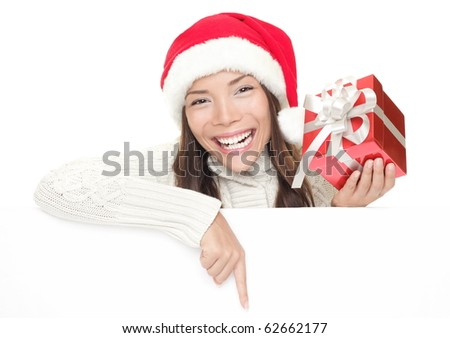 Christmas woman leaning over billboard sign. Pointing down holding gift showing big toothy smile. Caucasian / Asian woman wearing Santa hat and winter sweater isolated on white background. - stock photo