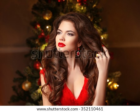 Christmas Woman. Long hair. Fashion earrings. Makeup. Beautiful girl portrait. Elegant lady in red dress with wavy healthy hairstyle over christmas tree xmas background. Happy new year. - stock photo