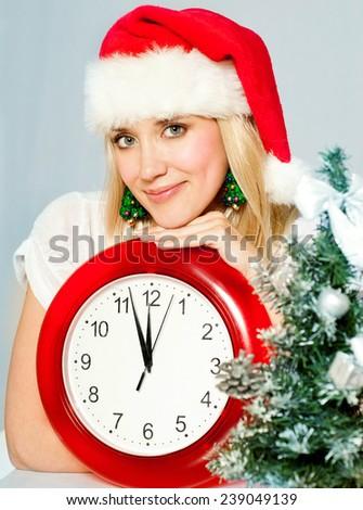 Christmas Woman. New Year and Christmas Tree Santa claus hat.clock. Winter season. - stock photo