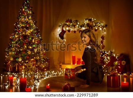 Christmas Woman Open Present Gift Box In Xmas Room, Holiday Tree Illuminated With Candles Lights - stock photo