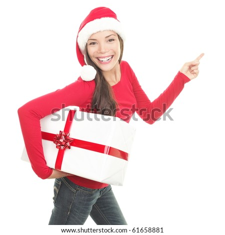 Christmas woman pointing up to the side at copy space. Isolated on white background. Beautiful young smiling woman in red Santa hat showing copyspace. Asian Chinese / white Caucasian female model. - stock photo