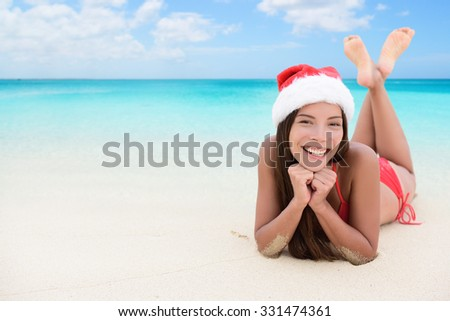 Christmas woman relaxing during winter beach holidays. Girl smiling at camera during travel vacation wearing a santa hat. Young mixed race adult in her 20s. - stock photo