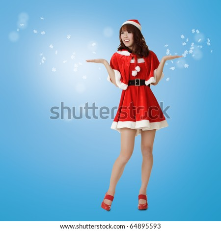 Christmas woman showing happy and surprised expression in dream with snowflakes over blue background. - stock photo