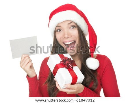 Christmas woman smiling excited holding gift and blank sign with copy space. Beautiful young smiling woman in Santa hat showing paper card sign. Caucasian / Asian model isolated on white background. - stock photo