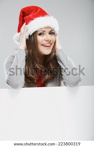 Christmas woman, white banner against gray background. White advertising board. Red santa hat on beautiful girl. - stock photo