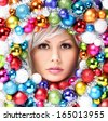 Christmas Woman with Colored Balls. Face of Beautiful Girl with Fashion Makeup and Shiny Christmas Baubles. - stock photo